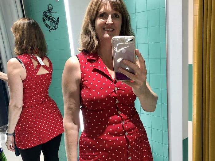 Jane wearing red polka dot top with pretty straps at Beyond Retro Vintage shop in Bristol