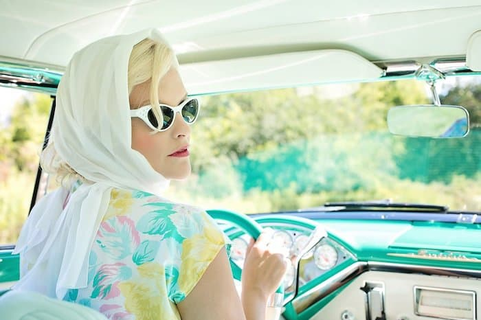 Glamorous lady driving in fifties fashion